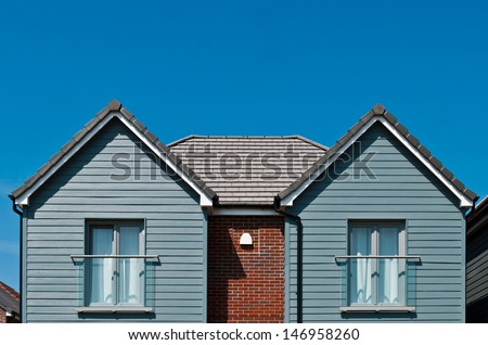 detached british residential house (beach style) with window baconies (blue sky) - stock photo