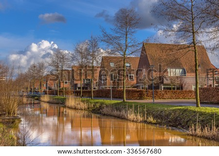 Detached middle class family houses in a natural ecological urban area in winter, Groningen, Netherlands