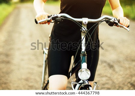 Detail . Bicycle  on road in golden light at sunrise or sunset. young girl with his bike. Woman riding a bicycle on a sun day. Sport. Healthy lifestyles concept