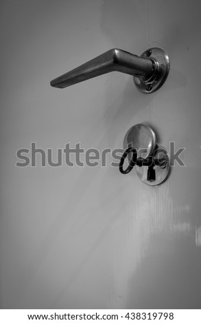 Detail - bottom view - of handle and lock with a key, locked doors, black and white photograph. - stock photo
