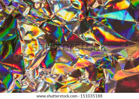 Detail close up of strongly wrinkled metallic paper as a colorful fantasy background image in rainbow colors with focus at the center - stock photo
