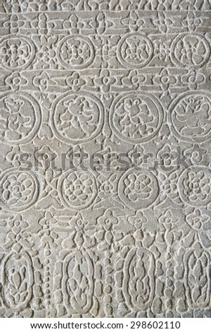 Detail close-up of the textured pattern of a carving in relief on a rough weathered stone wall at the Angkor Wat temple complex in Cambodia - stock photo