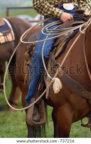Detail close up of Western Horse Saddle and Lasso rope, and Rodeo Cowboy in the saddle - stock photo