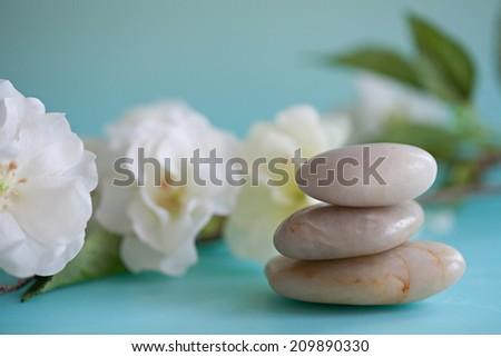 Detail close up still life view of a pile of natural smooth white stones balancing in a stack against white blossom flowers in a blue health spa background Nature objects and zen energy. - stock photo