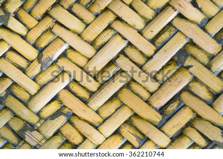 Detail close up view of a uniform golden woven basket using natural branch materials.Pattern of Thai style bamboo handcraft texture background with squares. - stock photo