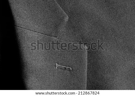 Detail closeup close-up of suit jacket lapel button hole fabric - stock photo