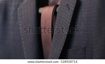 Detail closeup close-up of suit jacket lapel button hole fabric, selective focus
