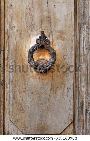 Detail embossed metal handle and an old door