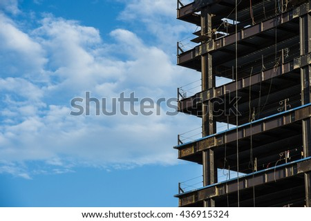 detail high rise building showing steel girders under construction with blue sky and white clouds - stock photo