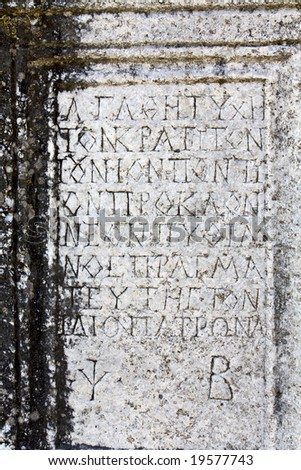 Detail image of an ancient plaque made by marble with ancient greek letters incised on its surface - stock photo