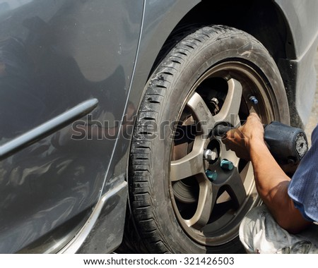 Detail image of hands with tool, changing tyre of car, repair car on daytime