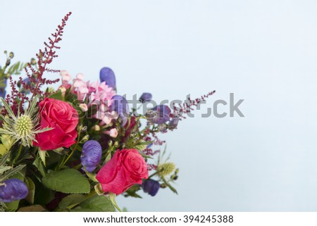 Detail mixed bouquet flowers on blue background - stock photo