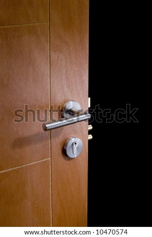 detail of a an open door whit lock handle, and black background