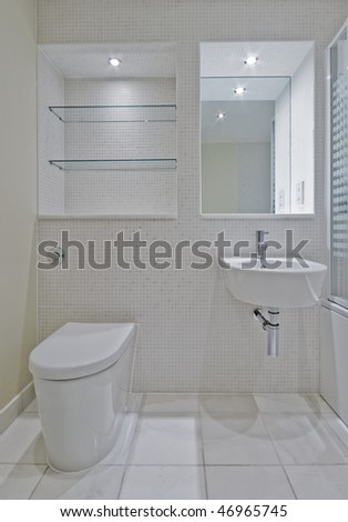 detail of a bathroom with white ceramic suite and mosaic tiles - stock photo