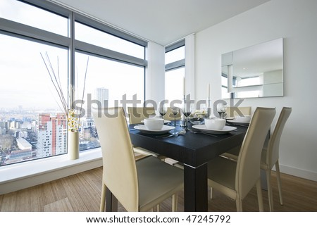 Detail of a beautiful dining area with wooden dining table and designer beige leather chairs - stock photo