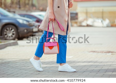 Detail of a beautiful young fashionable woman in blue trousers and a beige trench with a colored handbag.