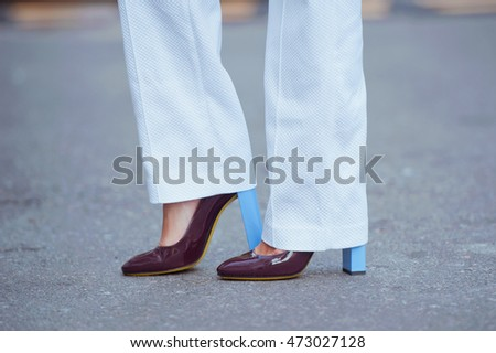 Detail of a beautiful young woman in white pants and shoes with high heels.