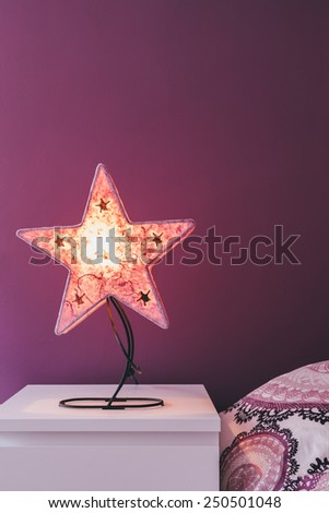 Detail of a Bedroom in Purple Colors with a Star Shaped Lamp - stock photo