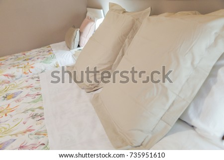 Detail of a bedroom, interior room. Double bed, individual bed and beige pillows