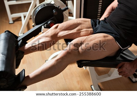 detail of a bodybuilder hard training in the gym: machine leg extensions - stock photo