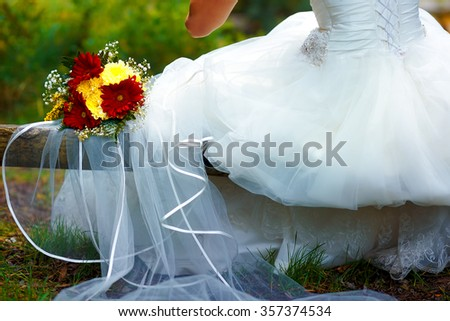 detail of a bride dress with a wedding bouquet outside - stock photo