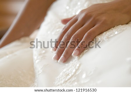 Detail of a bride touching her white dress