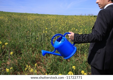 Detail of a business man with a blue watering can in a field - stock photo