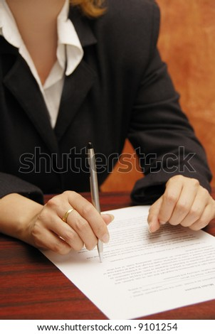 detail of a business woman with pen and contract to sign