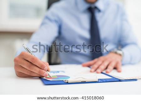 Detail of a businessman writing on a document - stock photo