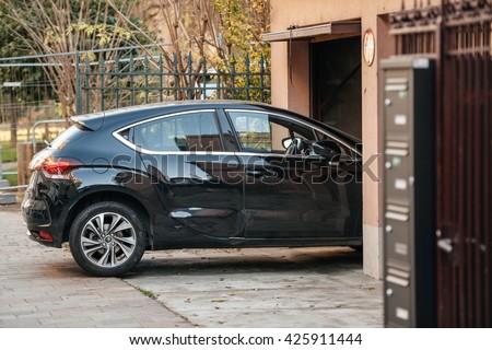 Detail of a car entering through garage door  - stock photo