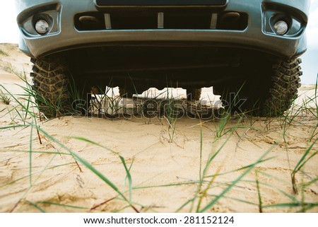 Detail of a car off-road, clearance vehicle, wheels with powerful protectors in the sand on the nature. - stock photo
