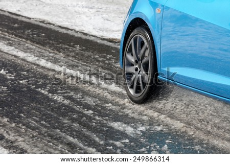 Detail of a car tire driving and splashing on the snow.  Driving on a snowy road. - stock photo