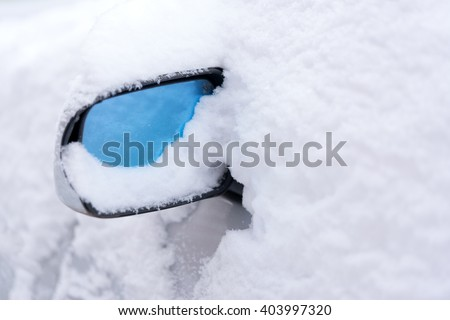 Detail of a car with a mirror covered with snow - stock photo