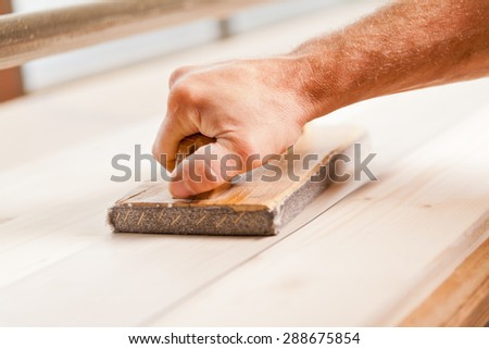 detail of a carpenter's hand wood-smoothing with belt sander - stock photo