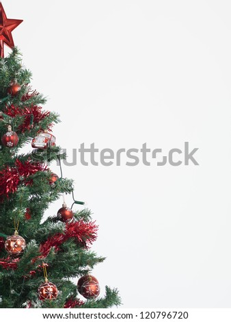 detail of a christmas tree decorated with red garland, globes and star isolated on white background framed in the left border of the image - stock photo