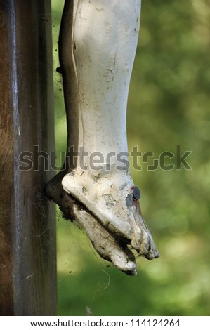 Detail of a crucifix - The feet of Jesus Christ nailed at a wooden cross - stock photo