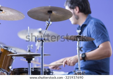 detail of a cymbal with an unfocused drummer playing drums on background in a recording studio - focus on the cymbal stand - stock photo