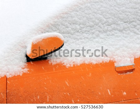 Detail of a dirty car with door and rear view mirror covered with thick layer snow during snowstorm