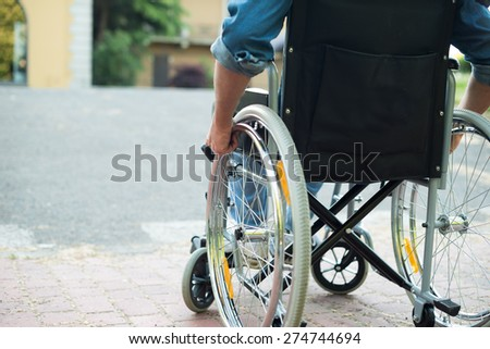 Detail of a disabled man trying to getting on a ramp - stock photo