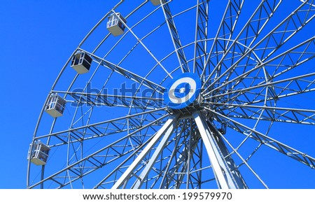 Detail of a ferris wheel on blue sky background