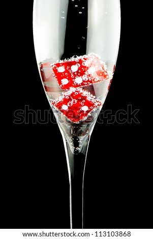 detail of a flute with two red dice and a lot of bubbles on black background - stock photo