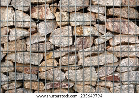 Detail of a gabion - grid basket with gray natural stones - which was built as a modern fence   - stock photo