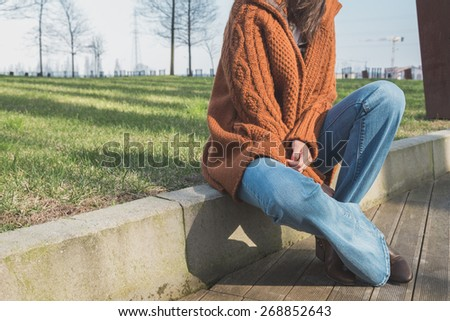 Detail of a girl with flared jeans posing in an urban context