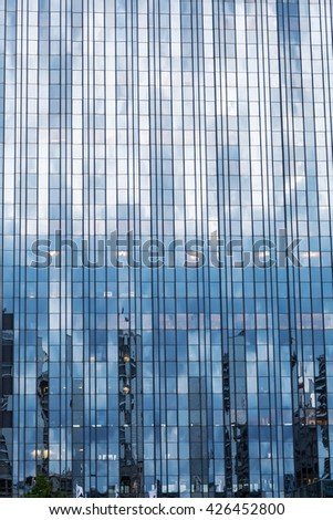detail of a glass facade of a highrise - stock photo
