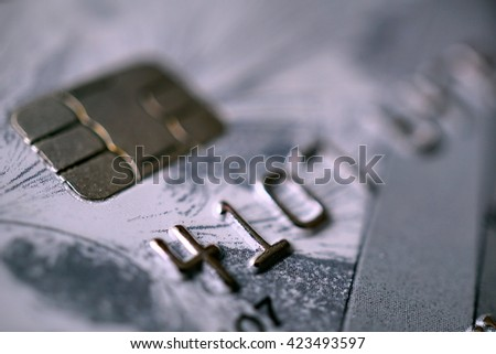 Detail of a gray plastic credit/debit card with its embossed numbers and letters and the electronic chip