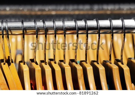 Detail of a group of many wooden clothes hangers together in store