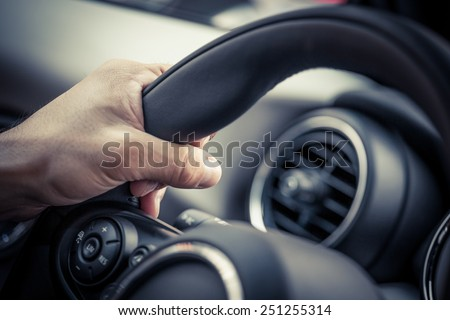 Detail of a hand holding a steering wheel. - stock photo