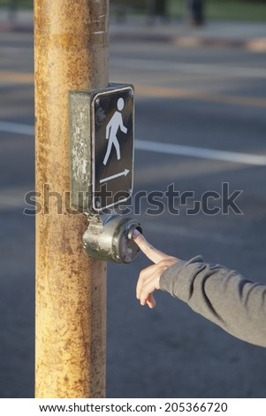 Detail of a hand pressing the button on pedestrian crossing - stock photo