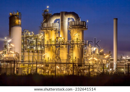 Detail of a heavy Chemical Industrial plant with mazework of pipes in twilight night scene - stock photo