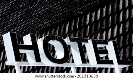 Detail of a hotel sign in front of a roof. - stock photo